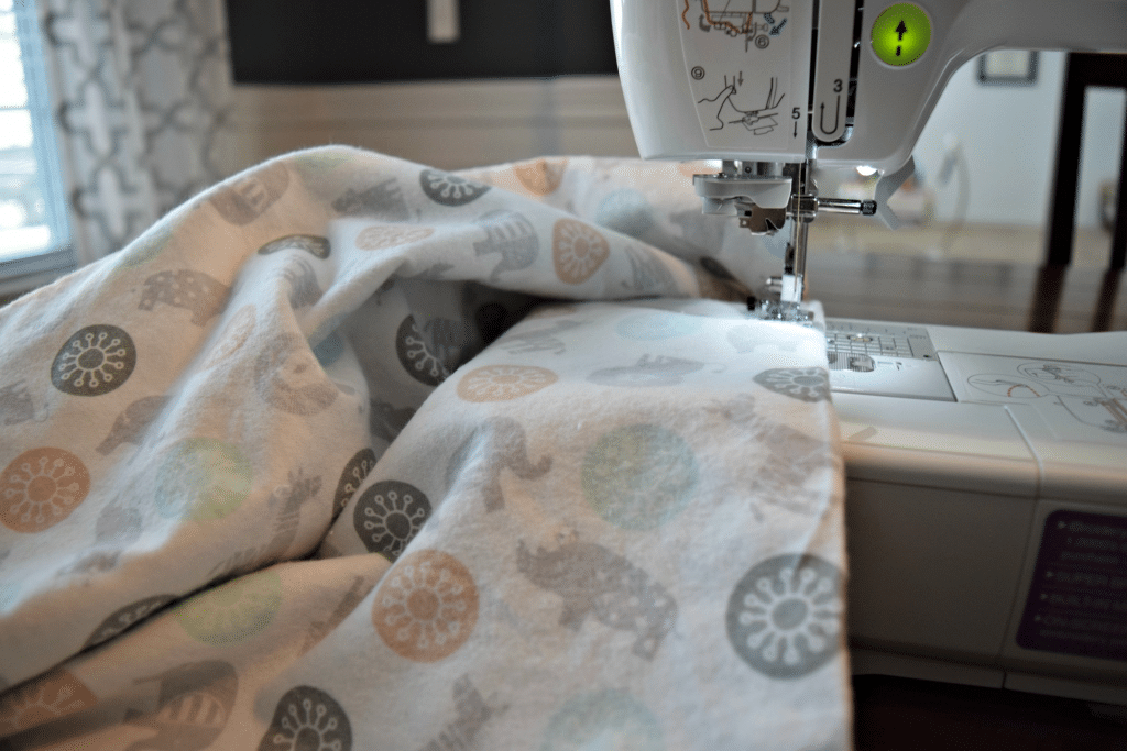 This adorable baby animal fabric is being sewed into a homemade baby blanket