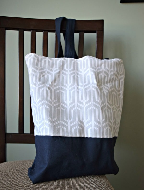 A diy canvas tote bag made with navy blue fabric and a grey and white printed fabric
