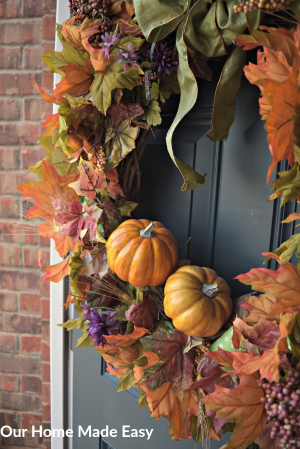 This fall wreath is packed with colorful leaves, ribbons, and pumpkins