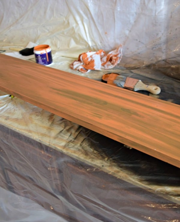 Paint the wood board your desired color. For a rustic look, use a light layer to let the stain show through