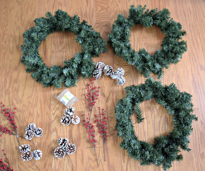 To make this super easy DIY Christmas wreath, all you need are some decorative picks like holly berries or pinecones, and a plain wreath