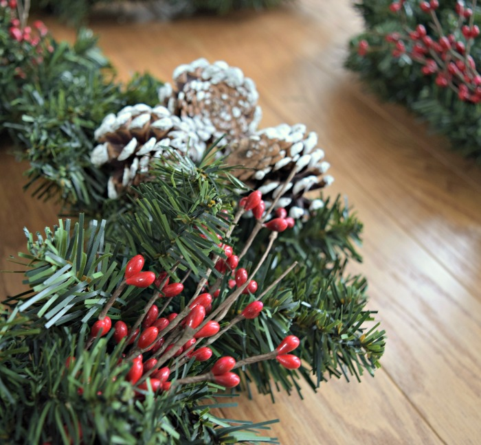 I love how easy it is to add fun seasonal accents to a Christmas wreath, like holly berries and frosted pine cones