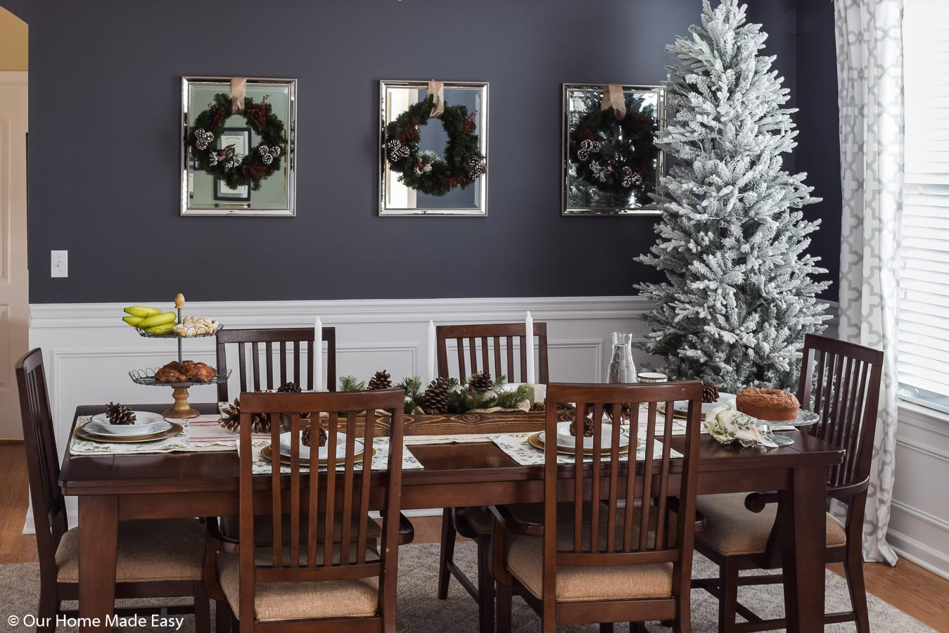 Our festive Christmas dining room is adorned with simple Christmas decor; wreaths, pinecones, and white-frosted Christmas tree