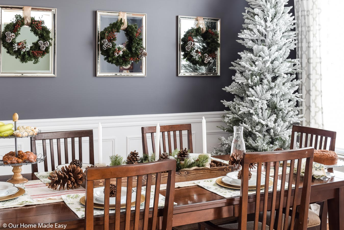 Our Christmas dining room is simple and bright, with a faux white-frosted Christmas tree, wreaths, and festive place settings