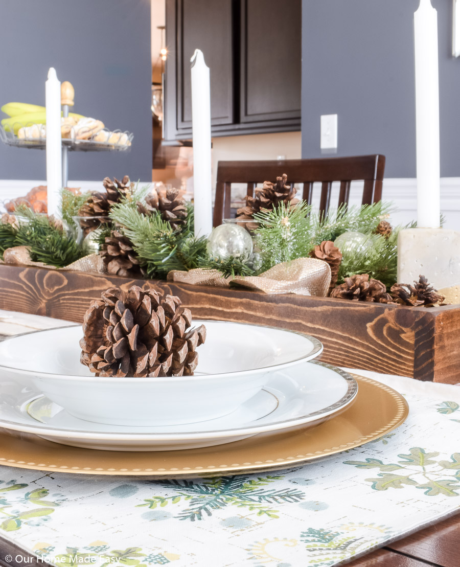 Our Christmas dining room table centerpiece is a simple DIY wood box filled with pinecones and faux fir tree branches