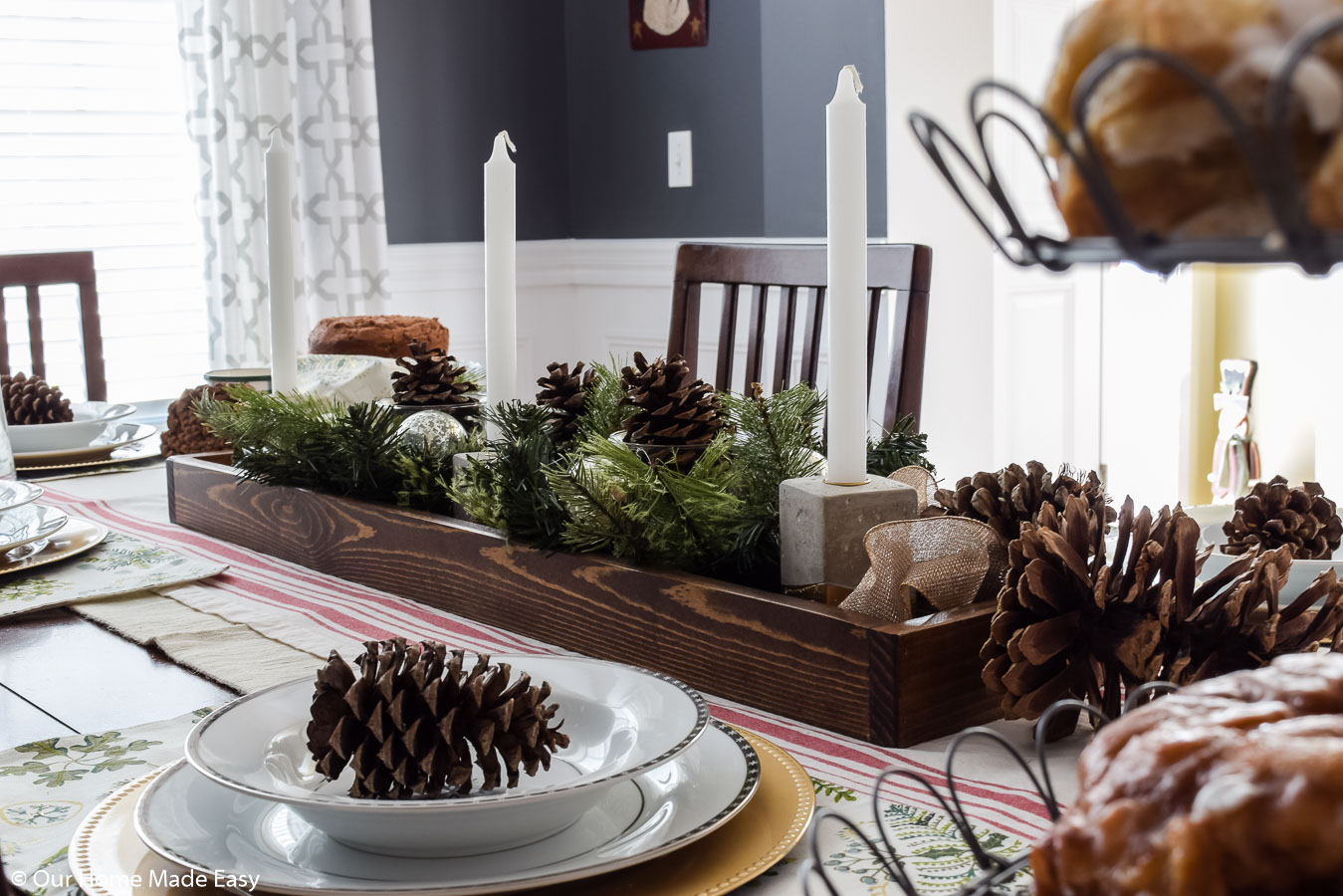 This simple DIY wood tray is perfect for centerpieces. We made a Christmas centerpiece with pinecones and faux fir branches