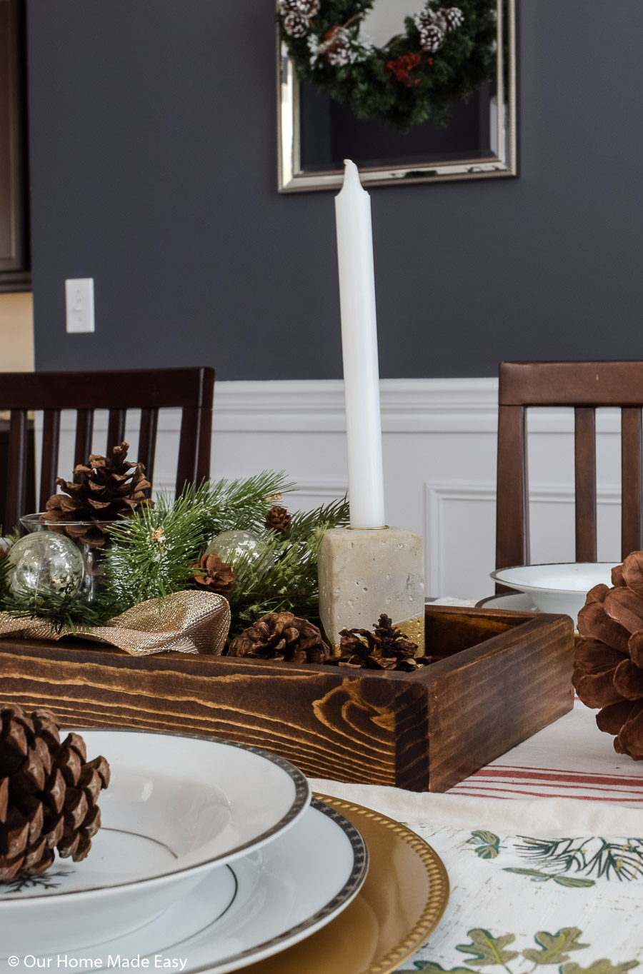 Our dining room table Christmas centerpiece has candlesticks, pinecones, and faux fir branches