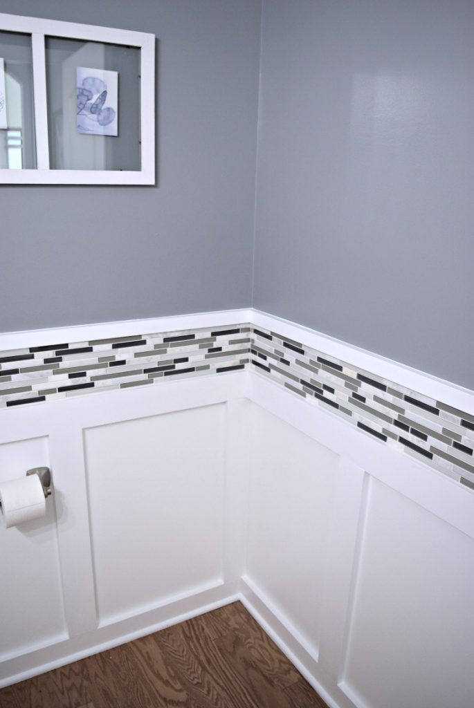 Batten board walls with a new black, white, and gray tile border and soft gray paint