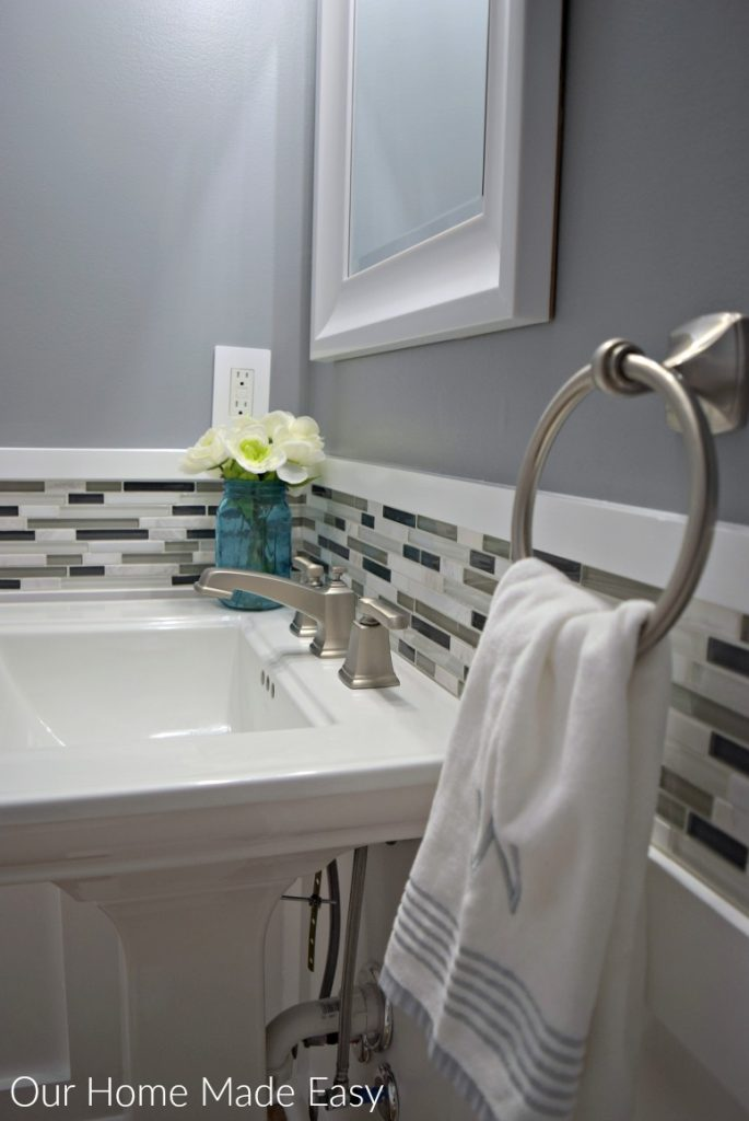 Black, white, and gray tile backsplash with gray walls and a white pedestal sink in our new powder room