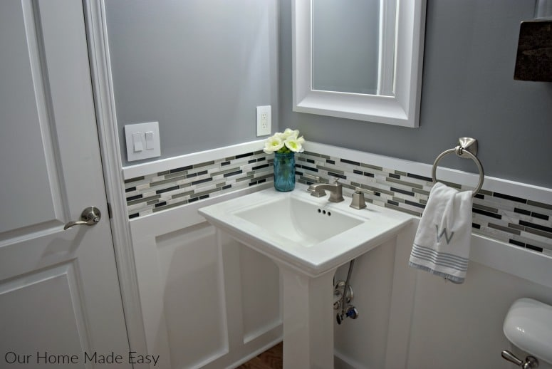 Here is an easy DIY budget powder room makeover! We used easy projects to go from builder grade to modern. Click to see how we did it!