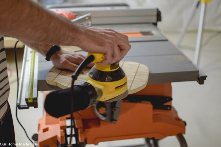Use an orbital sander to sand down and smooth out the surface and sides of the plywood pumpkin
