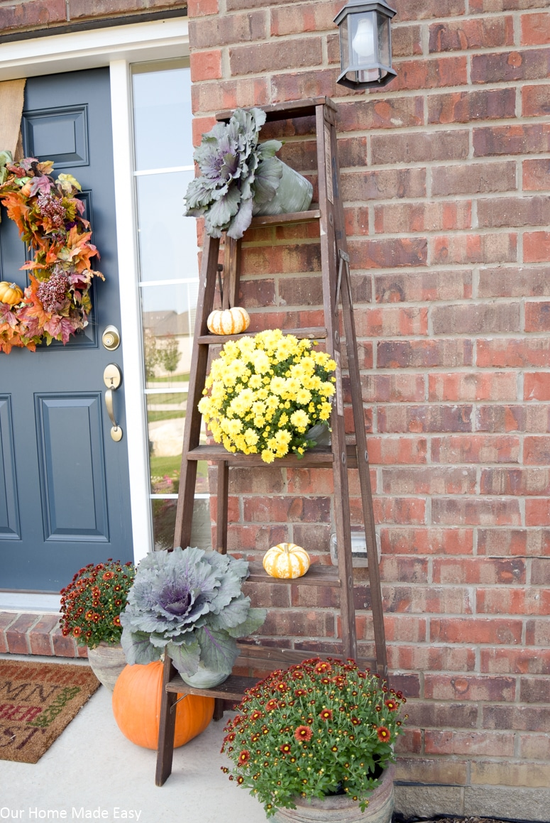 Simple rustic fall front porch with planted mums and pumpkins