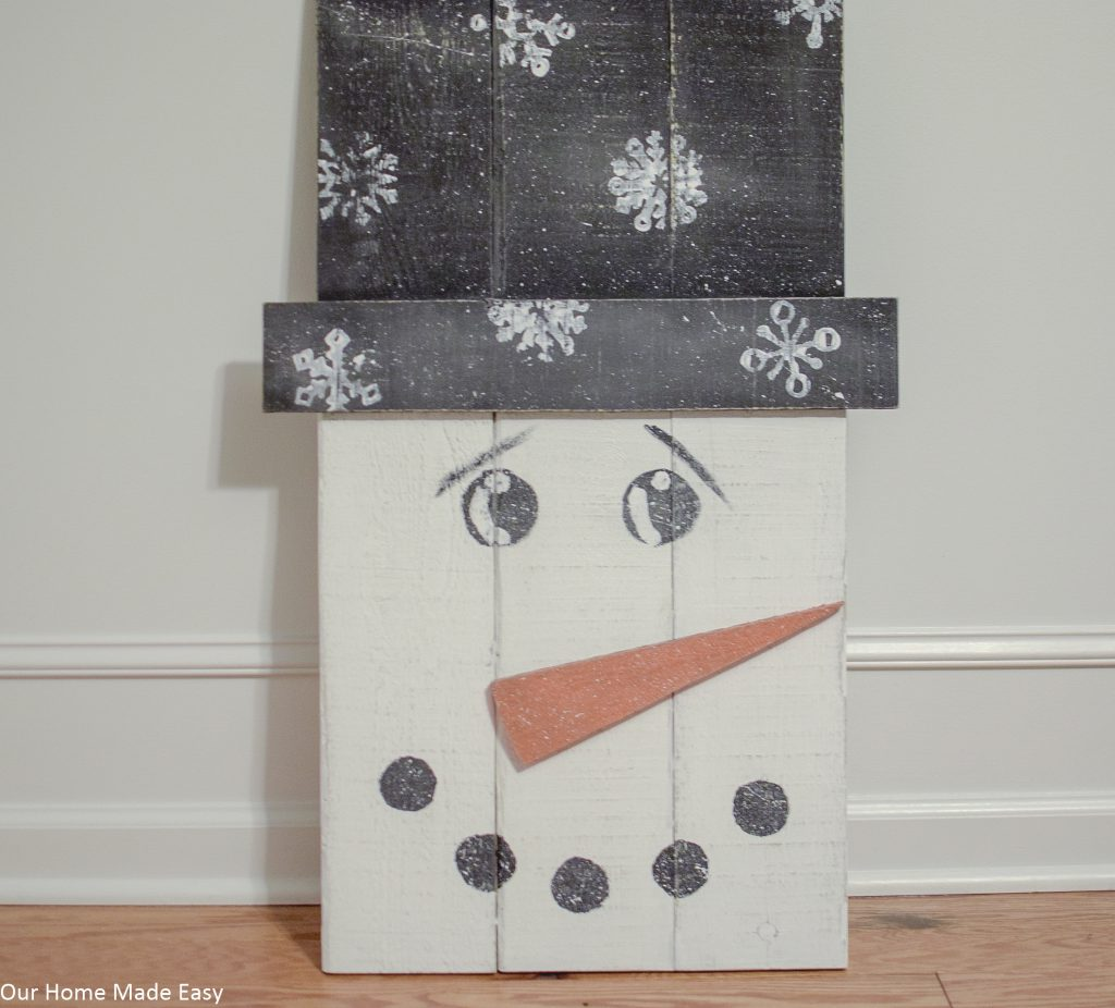 Make this super easy pallet snowman! Use some leftover paint and wood to build this easy DIY snowman. No fancy tools needed!