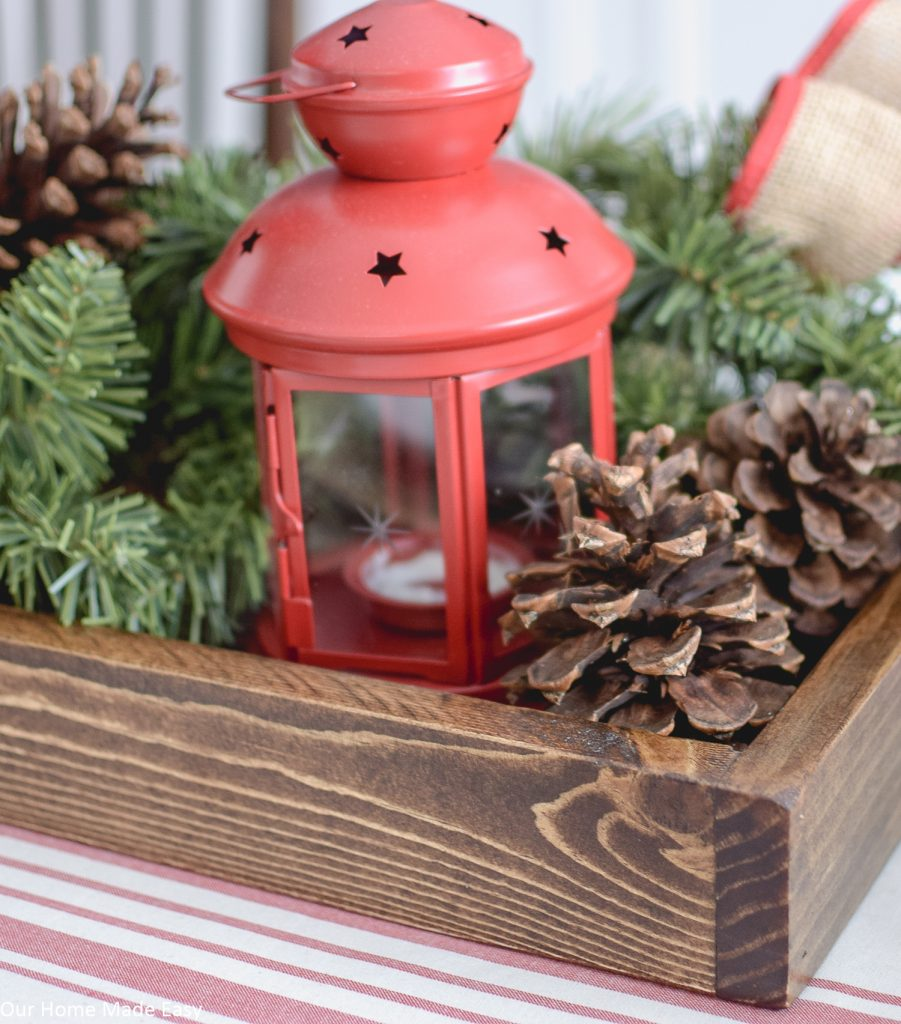 We used this wood serving tray as a Christmas centerpiece, filling it with a lantern, pine cones, and pine tree branches