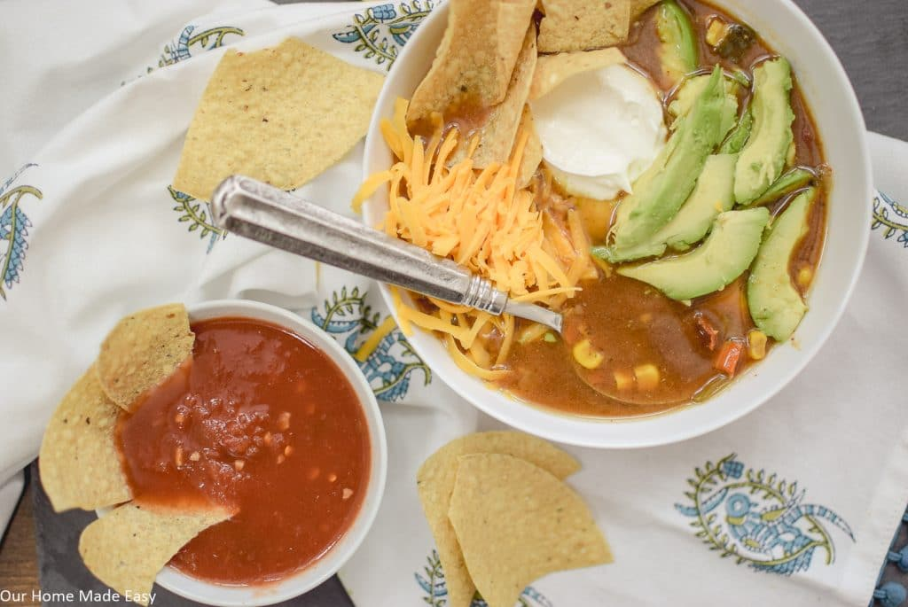 Serve this delicious slow cooker tortilla soup with some shredded cheese, soup cream, avocado, and of course, chips and salsa on the side!