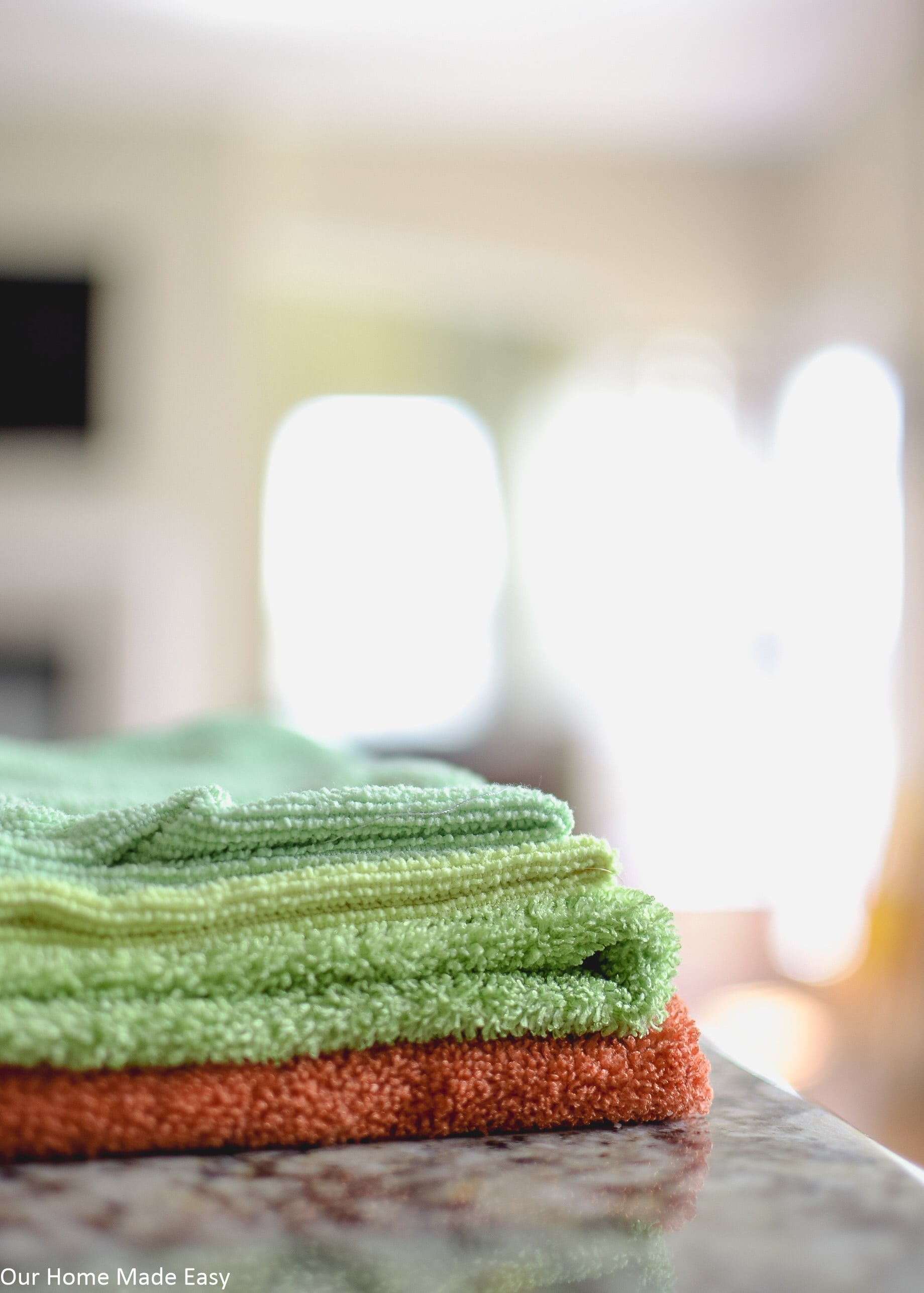 Folded microfiber towels in orange, green, yellow, and blue