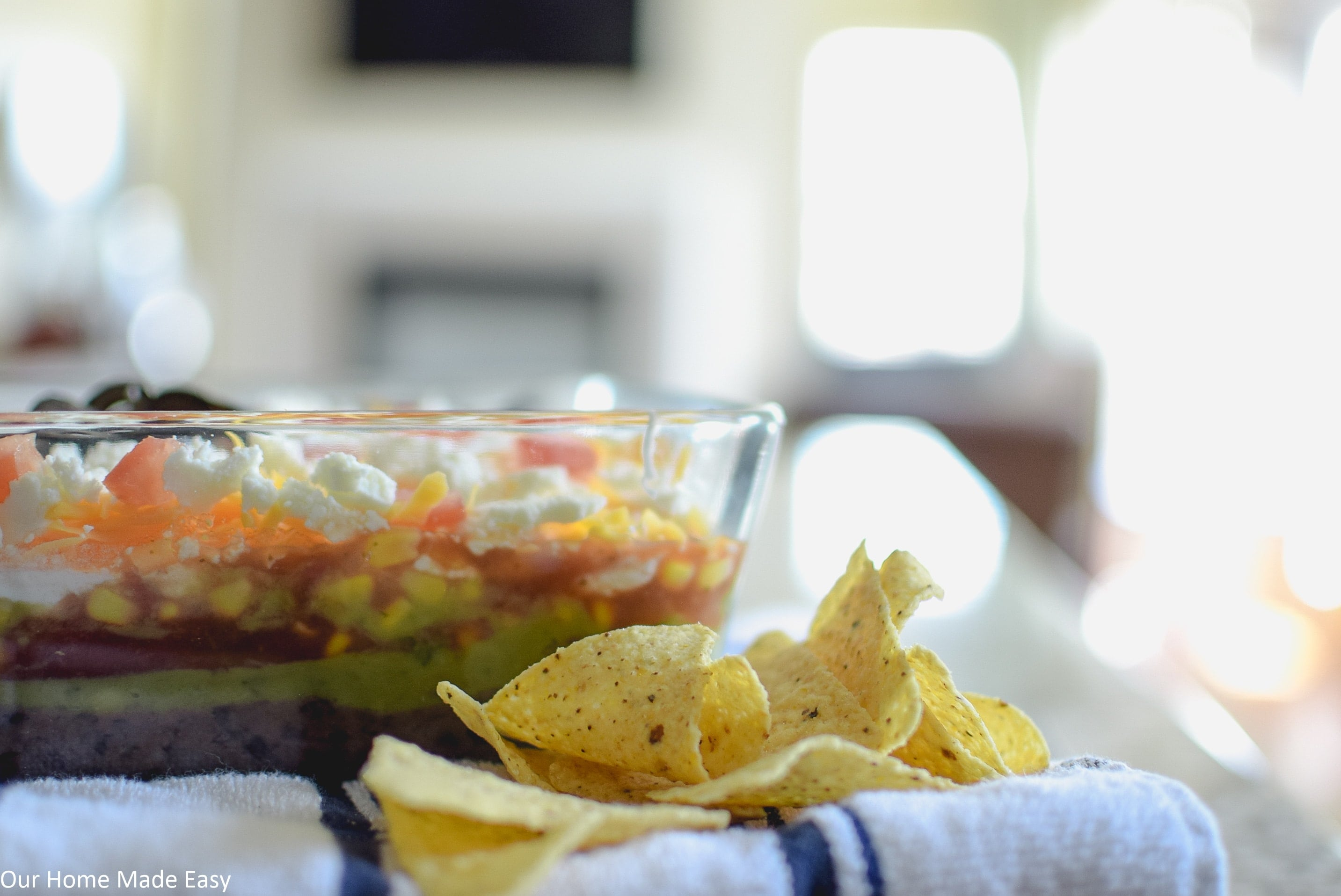 serve this 7 layer taco dip with chips for a delicious party appetizer