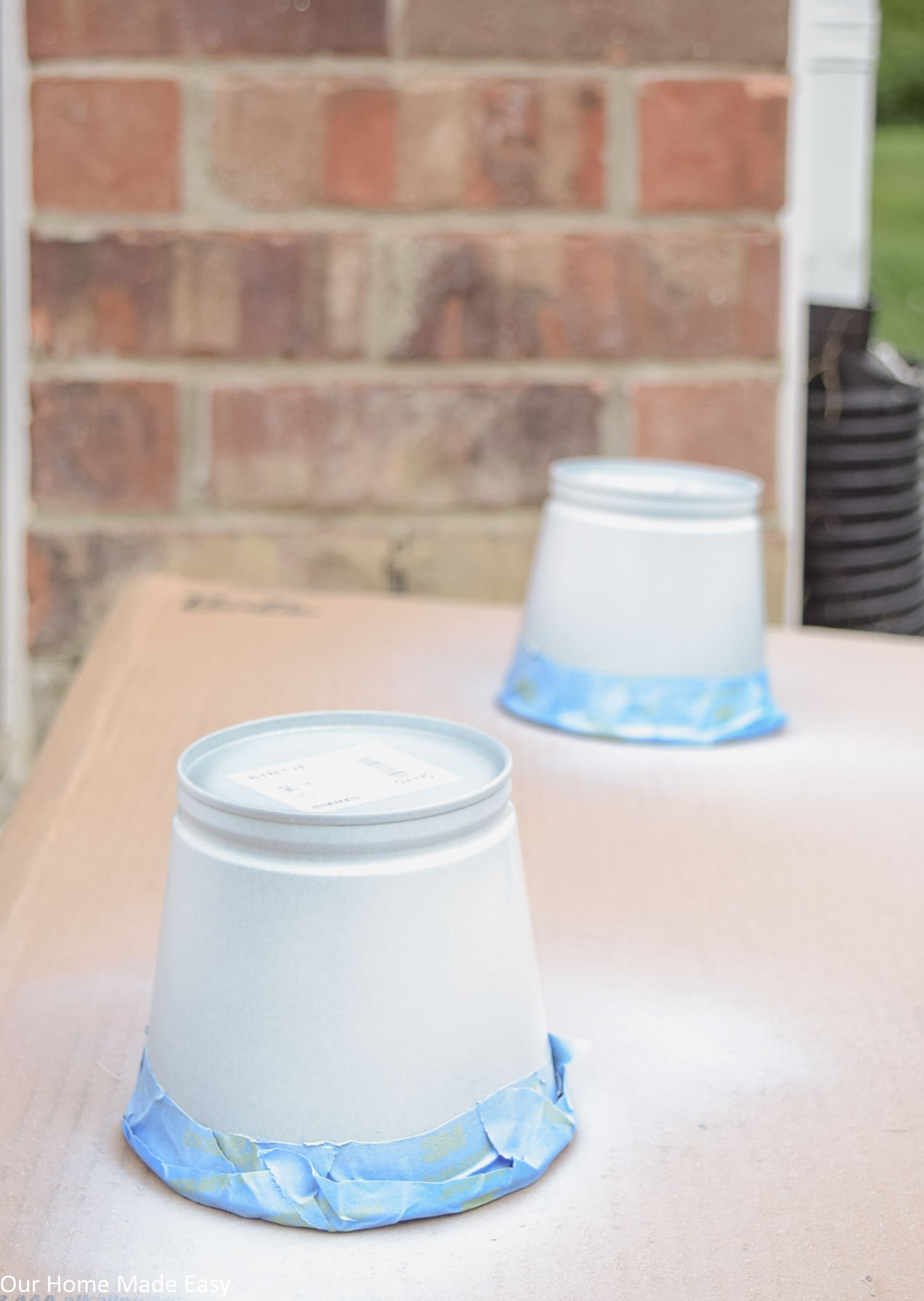 These metal planters receive their first coat of white Plasti Dip crafting spray paint