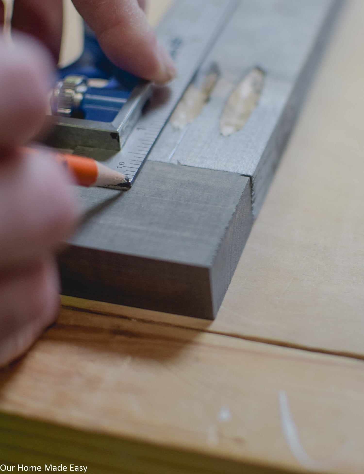 Using a ruler to measure out pocket screw holes and were to drill in the sign backboard