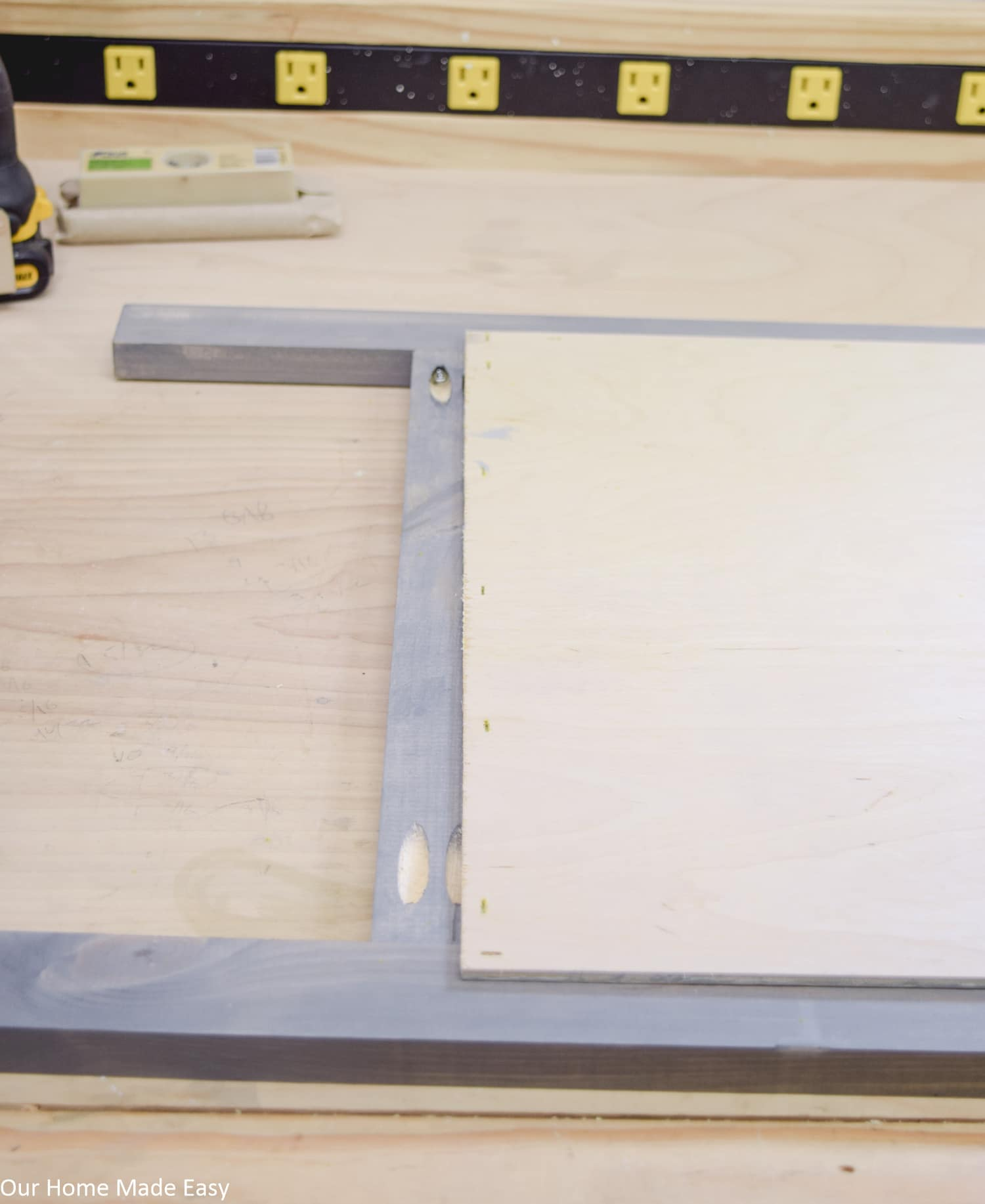 Pocket screws hold together the wooden sign frame, which we painted a rustic light blue gray