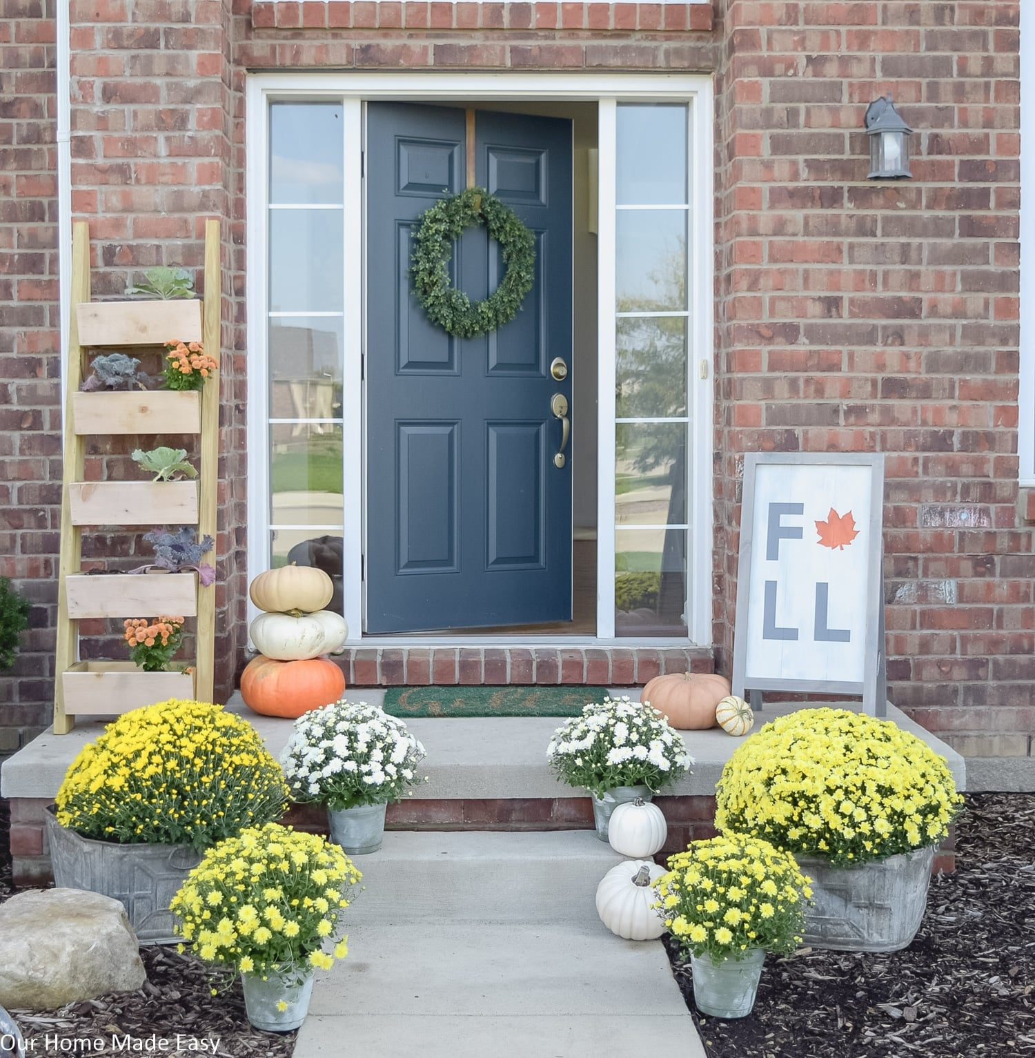 this inviting fall front porch is decorated with arrangements of bright colored mums