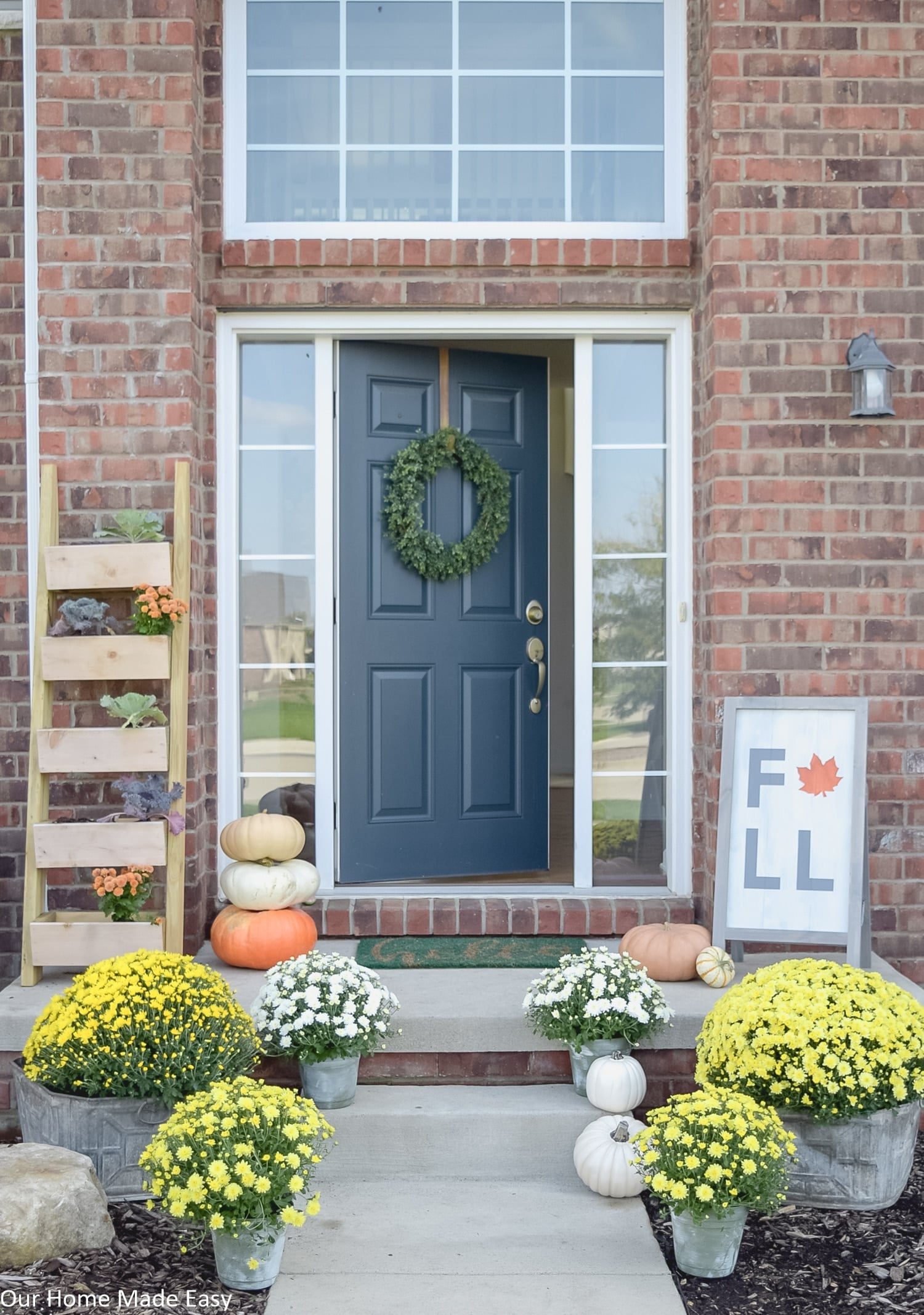 this fall themed front porch is decorated with yellow and white potted mums and harvest pumpkins