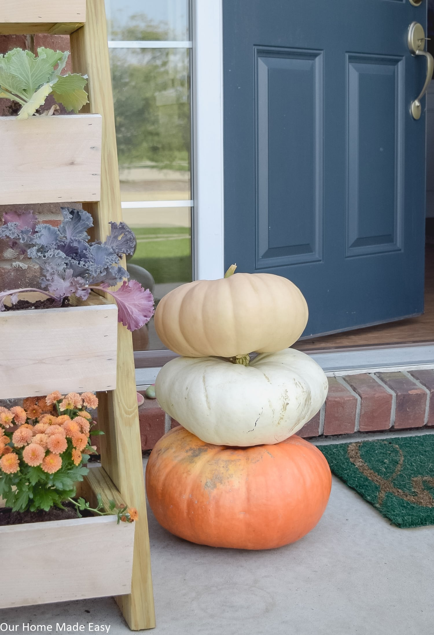 this simple fall front porch has small accents like pots of mums and harvest pumpkins