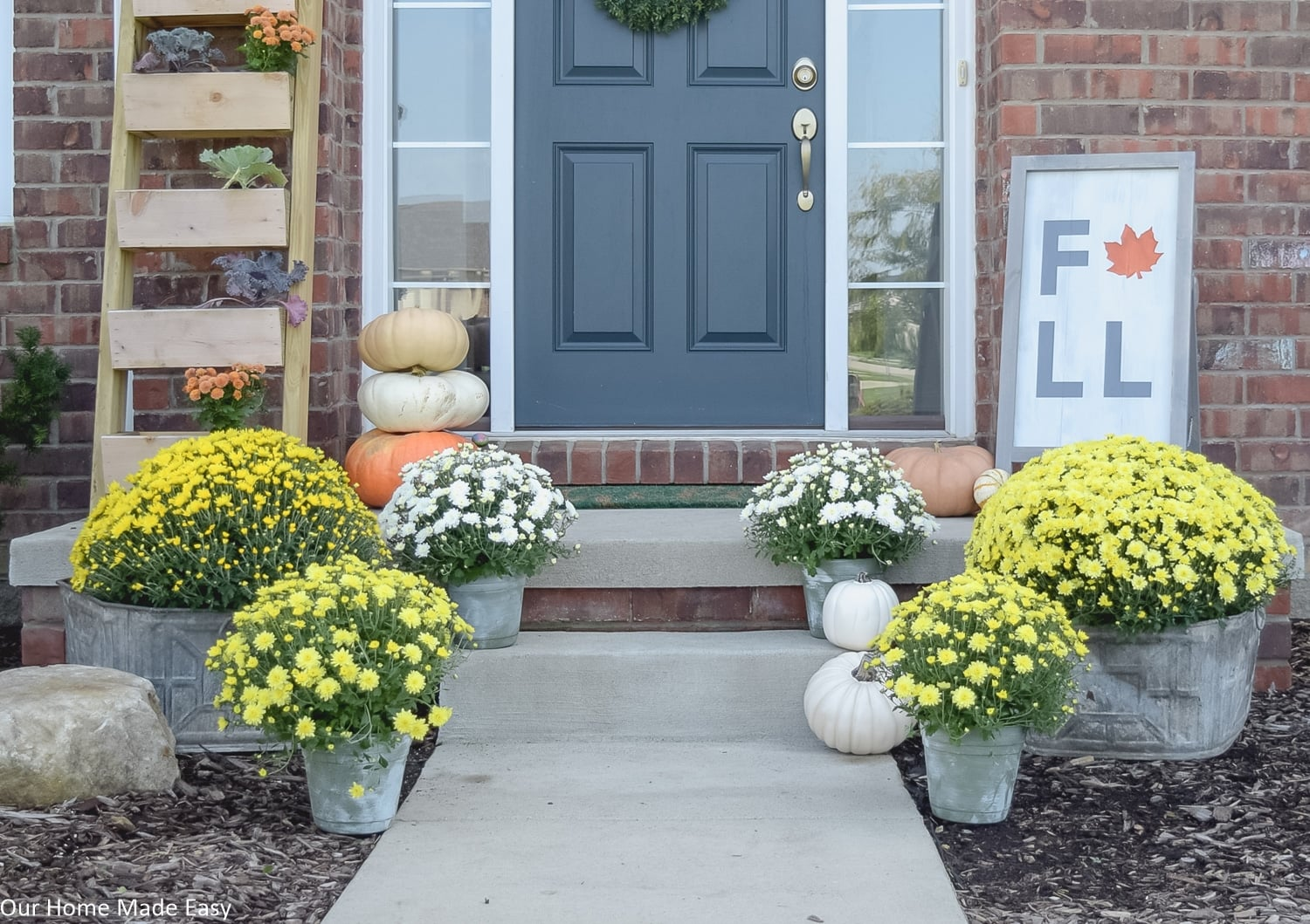 this fall themed front porch is warm and inviting with potted mums and harvest pumpkins
