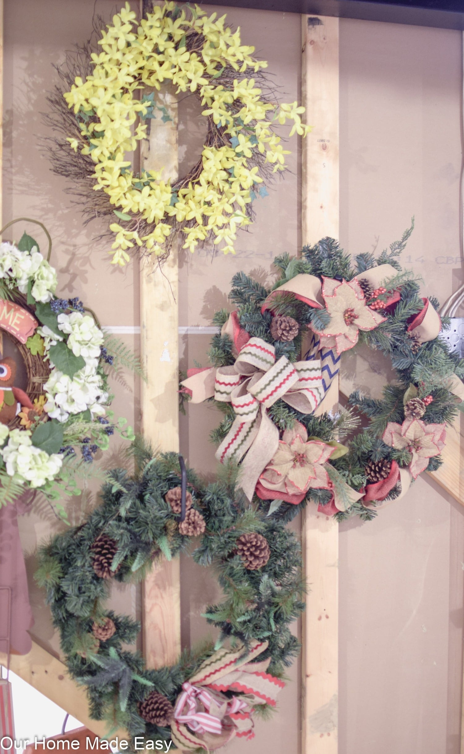organize holiday wreaths with hooks to keep them pretty throughout the year