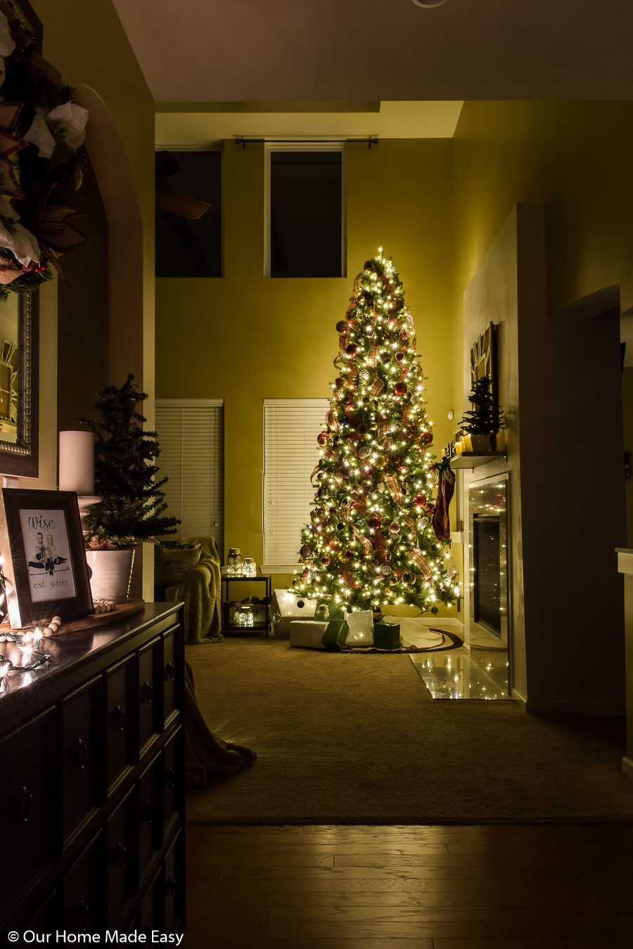 Our home's entry way has subtle Christmas decor, leaving the focus on the bright Christmas tree in the living room