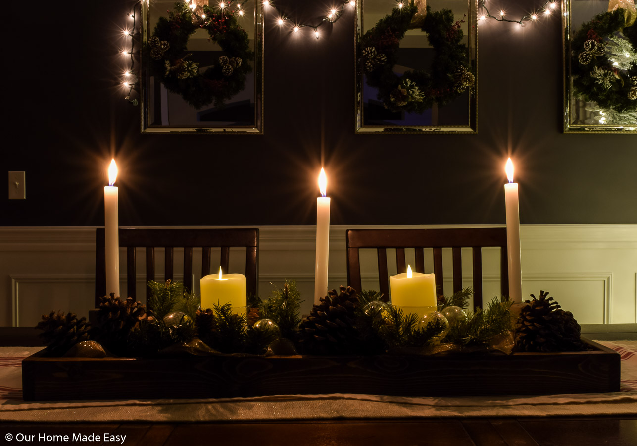 Our dining room table Christmas table centerpiece is brightened up with simple white candle sticks