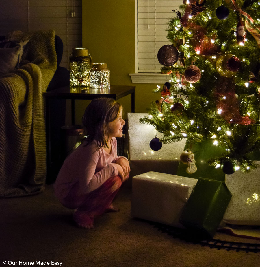 My youngest daughter, Aubrey, crouched in front of our living room Christmas tree, admiring the lights, ornaments, and presents