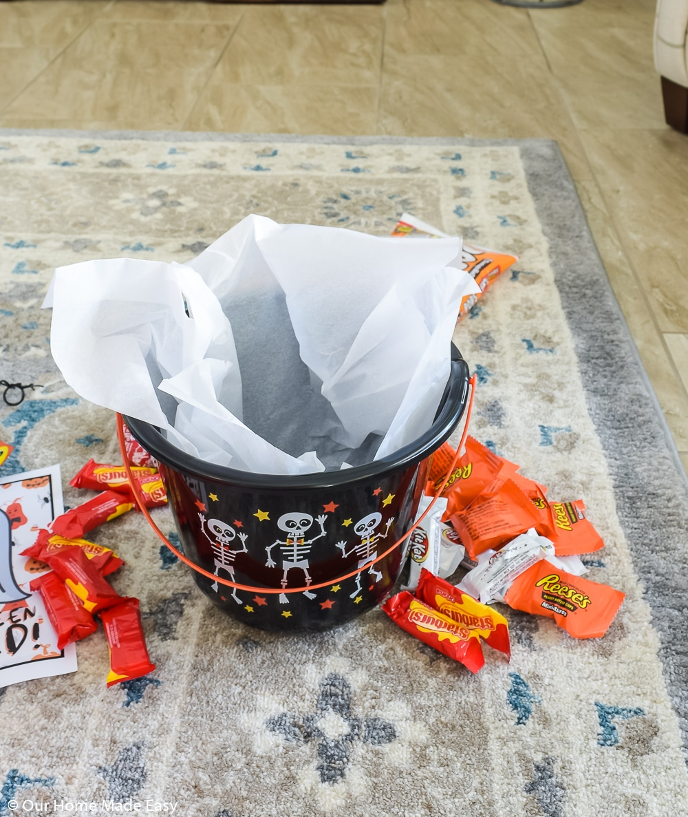 To make a You've Been Booed bucket, all you need is a Halloween bucket, candy, and some tissue paper.
